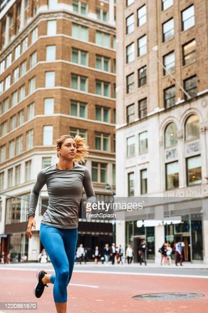 linda mulher loira correndo nas ruas de nyc - manga longa - fotografias e filmes do acervo
