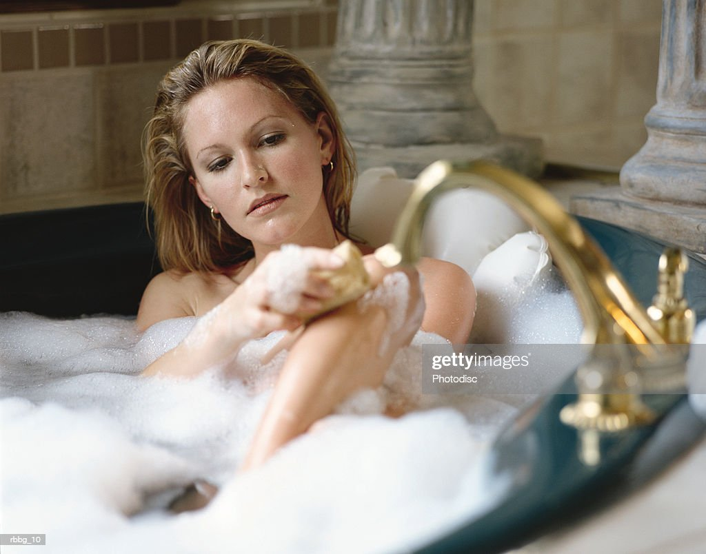 beautiful blonde woman scrubbing herself in bathtub with brass fixtures and pillars in background : Stockfoto