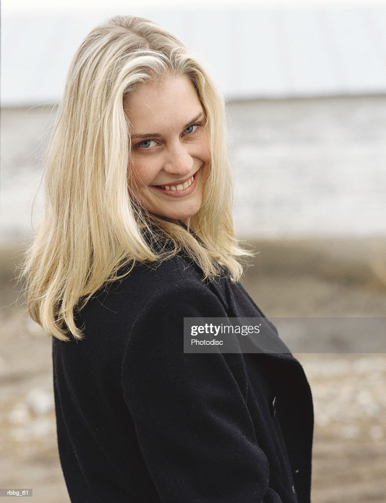Beautiful blonde woman standing on the beach : Stockfoto