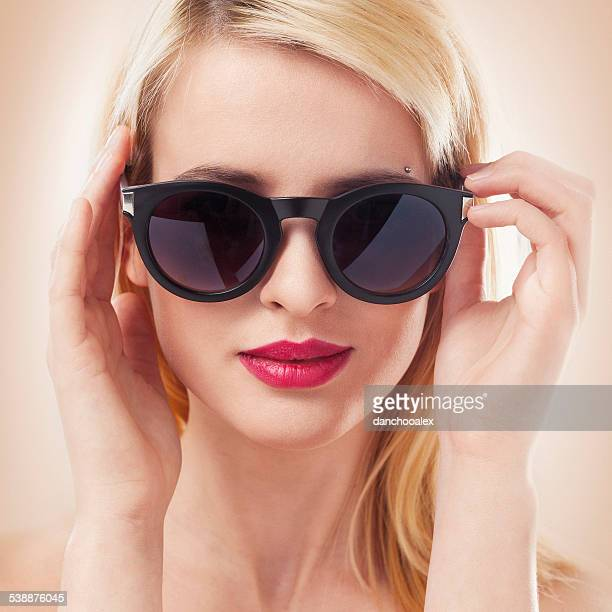 Beautiful blonde woman wearing sun glasses close up shot