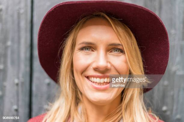 beautiful blonde woman with garnet hat portrait - mid adult stock pictures, royalty-free photos & images