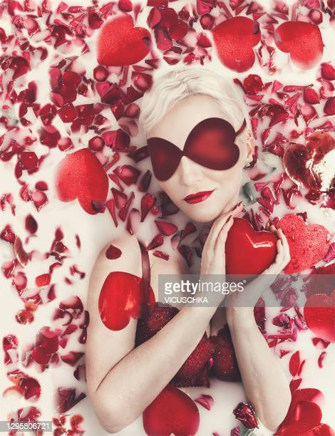 a beautiful blonde woman with red blindfolded, shape of hearts, red lingerie with bright red lips and a heart in her hands lies in a milk bath with red rose petals - damp lips stock pictures, royalty-free photos & images