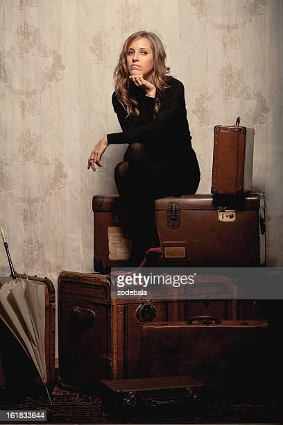 美しいブロンド WomanTraveller ウェイティングの古いバッグ