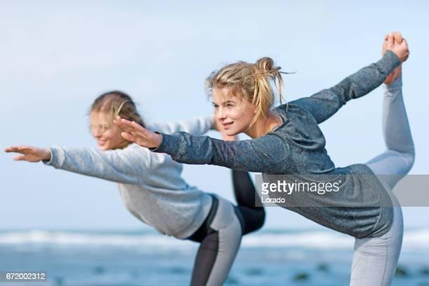 Instructeur d'yoga blonde beau travail avec un ami sur une plage pendant la journée