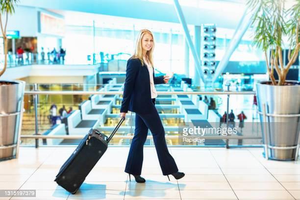 belle jeune femme d'affaires blonde remorquant sa valise par un aéroport - mezzanine photos et images de collection
