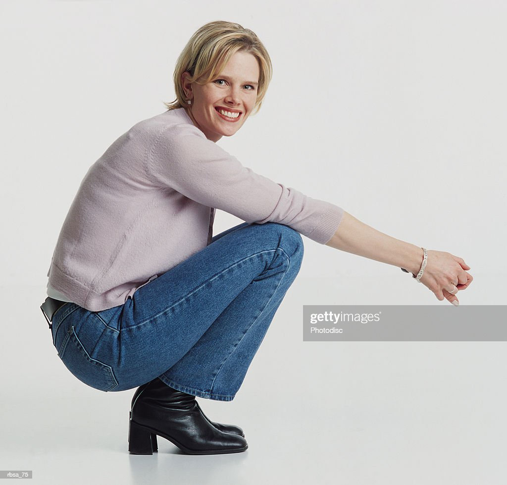 beautiful blonde young caucasian adult female wearing a pale pink sweater and jeans squating on the floor facing sideways with arms stretched forward as she looks towards the camera smiling : Foto de stock