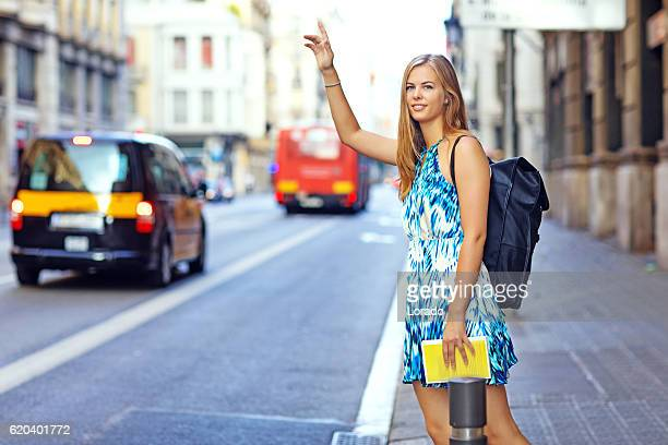 Beautiful blonde young woman student hailing cab in european city