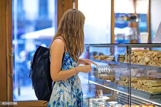 Beautiful blonde young woman student shopping in daytime european bakery