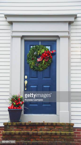 beautiful blue front door decorated for christmas - country christmas stock pictures, royalty-free photos & images