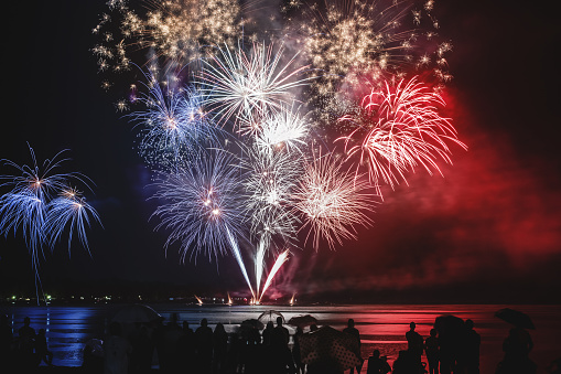 Beautiful blue white and red firework pyrotechnics show like french flag colors with unrecognizable crowd silhouettes watching 838902516