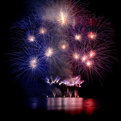 Beautiful blue white and red large fireworks with water reflections 599996500