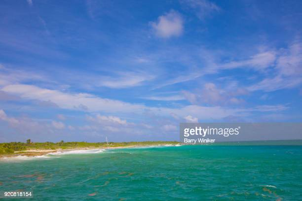 Beautiful blue-green color to Caribbean Sea under blue and white sky near shoreline of the Yucatan, Mexico