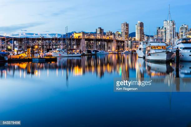 Beautiful boats docked at twilight with Burrard Street Bridge in Vancouver, Canada.
