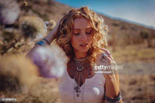 Beautiful bohemian girl day dreaming in field at sunset