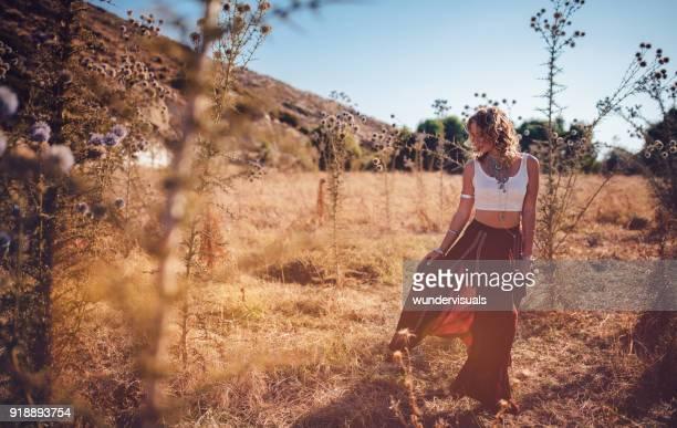 Beautiful bohemian woman in red skirt relaxing in field