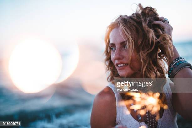 Beautiful boho girl celebrating with sparklers at beach at sunset