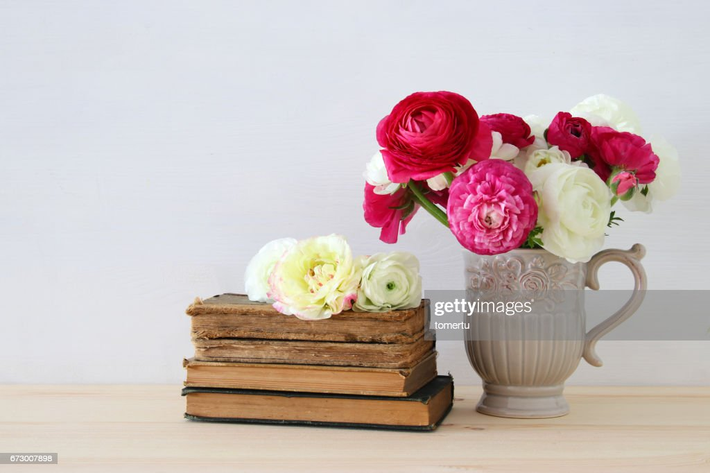 Beautiful Bouquet Of Flowers In The Vase Next To Old Books Stock
