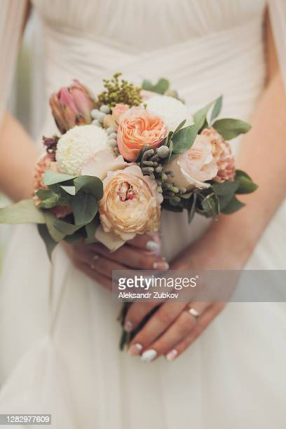 beautiful bouquet with pink and white roses in the hands of a girl or woman. the bride in a luxurious expensive elegant dress holds a wedding bouquet in her hands. - cérémonie photos et images de collection