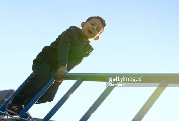 Beautiful boy climbing frame in playground