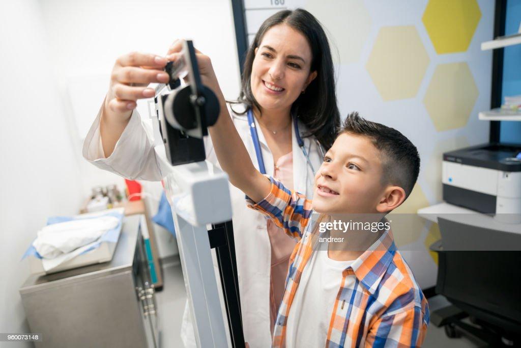 Schöne junge weibliche Kinderarzt, um die Waage passen beide auf der Suche sehr glücklich zu helfen : Stock-Foto