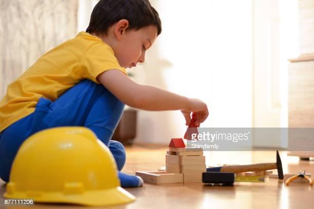 lindo menino está brincando com blocos de brinquedo e ferramentas manuais - coluna de madeira - fotografias e filmes do acervo