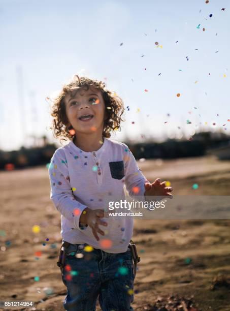 Mooie jongen lachen onder confetti