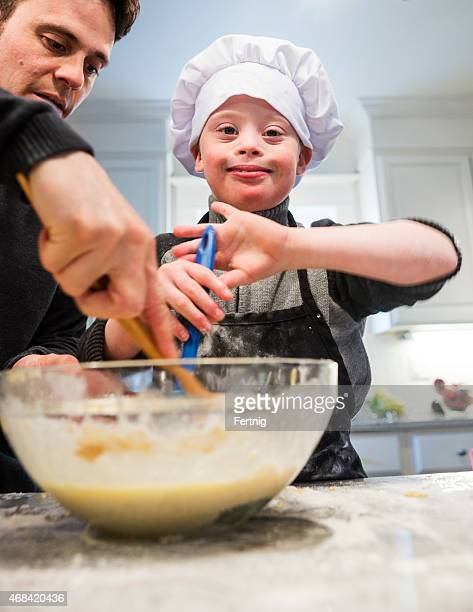 Beautiful boy with Down Syndrome baking with dad.
