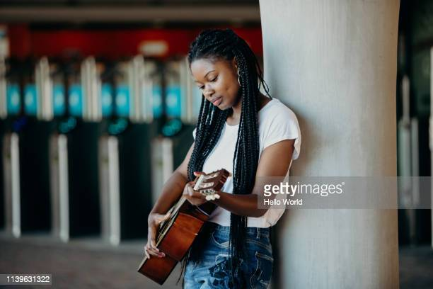 beautiful braided hair young woman playing guitar whilst leaning against a pillar - street artist stock pictures, royalty-free photos & images