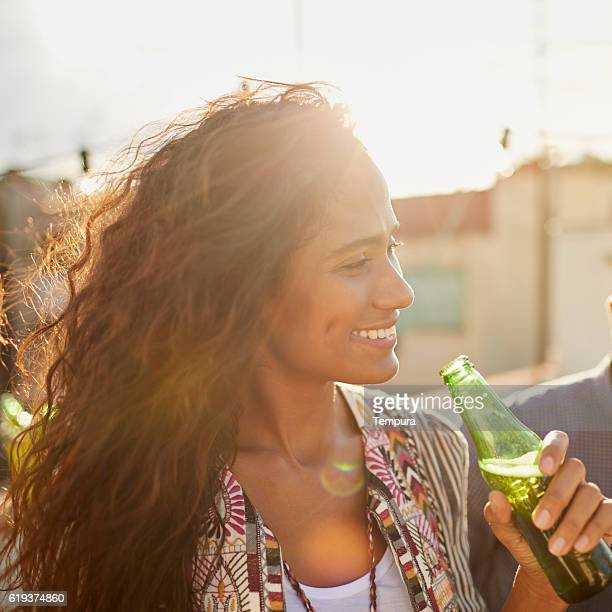 Beautiful Brazilian woman drinking beer from a bottle.