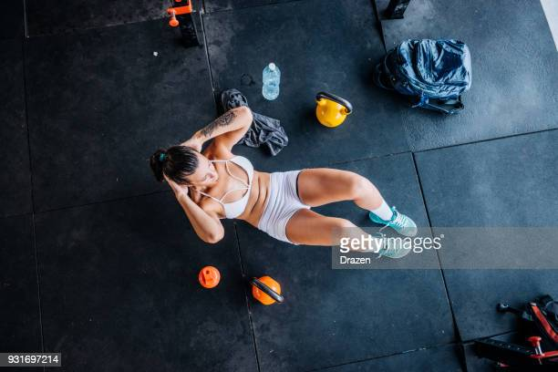 beautiful brazilian woman exercising abs on cross training - circuit training stock photos and pictures