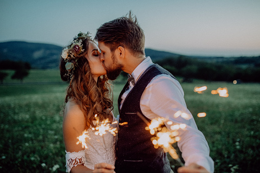Beautiful bride and groom with sparklers on a meadow. 929489874