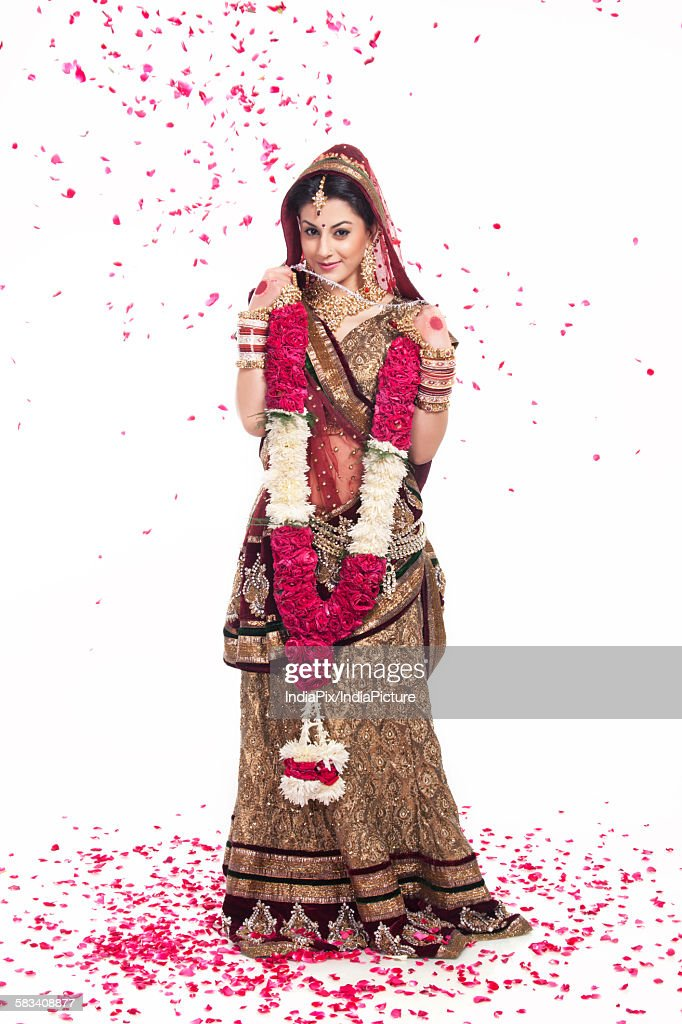 Beautiful bride holding a garland : Stock Photo