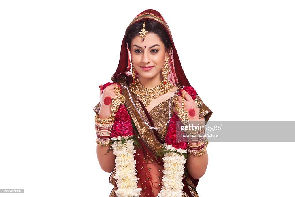Beautiful bride holding a garland : Stock Photo