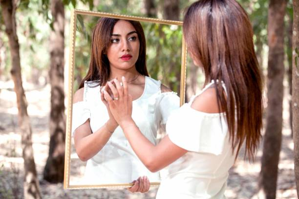 Beautiful Bride Holding Mirror With Reflection Against Trees