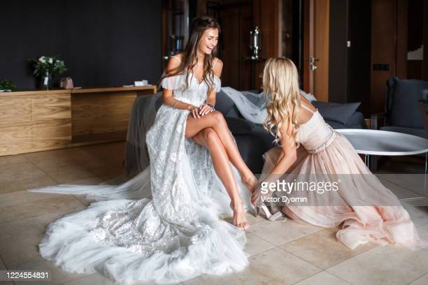 beautiful bride is getting ready with her bridesmaid - bridesmaid stock pictures, royalty-free photos & images