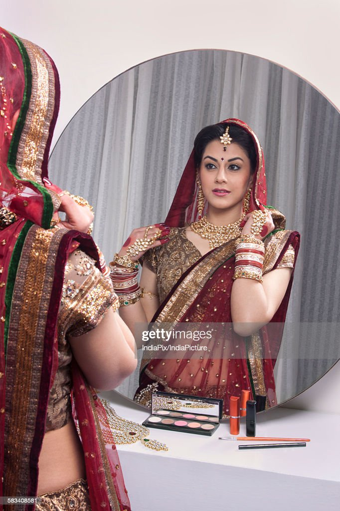Beautiful bride looking at herself in mirror : Stock Photo