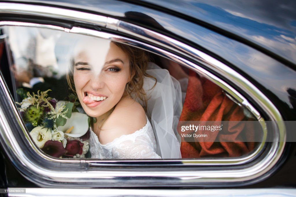 Beautiful bride shows tongue sitting in the car : Stock Photo
