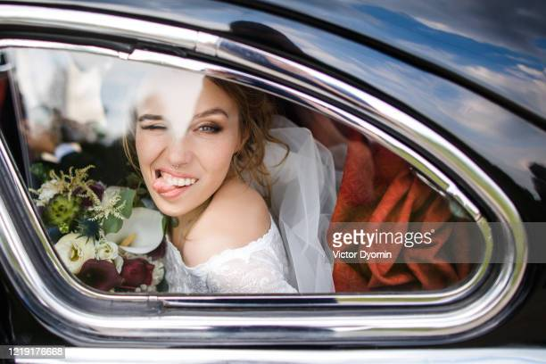 beautiful bride shows tongue sitting in the car - bride stock pictures, royalty-free photos & images