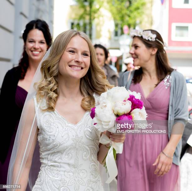 beautiful bride with her maids of honor on street