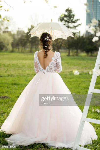 Hermosa novia con paraguas, vista trasera