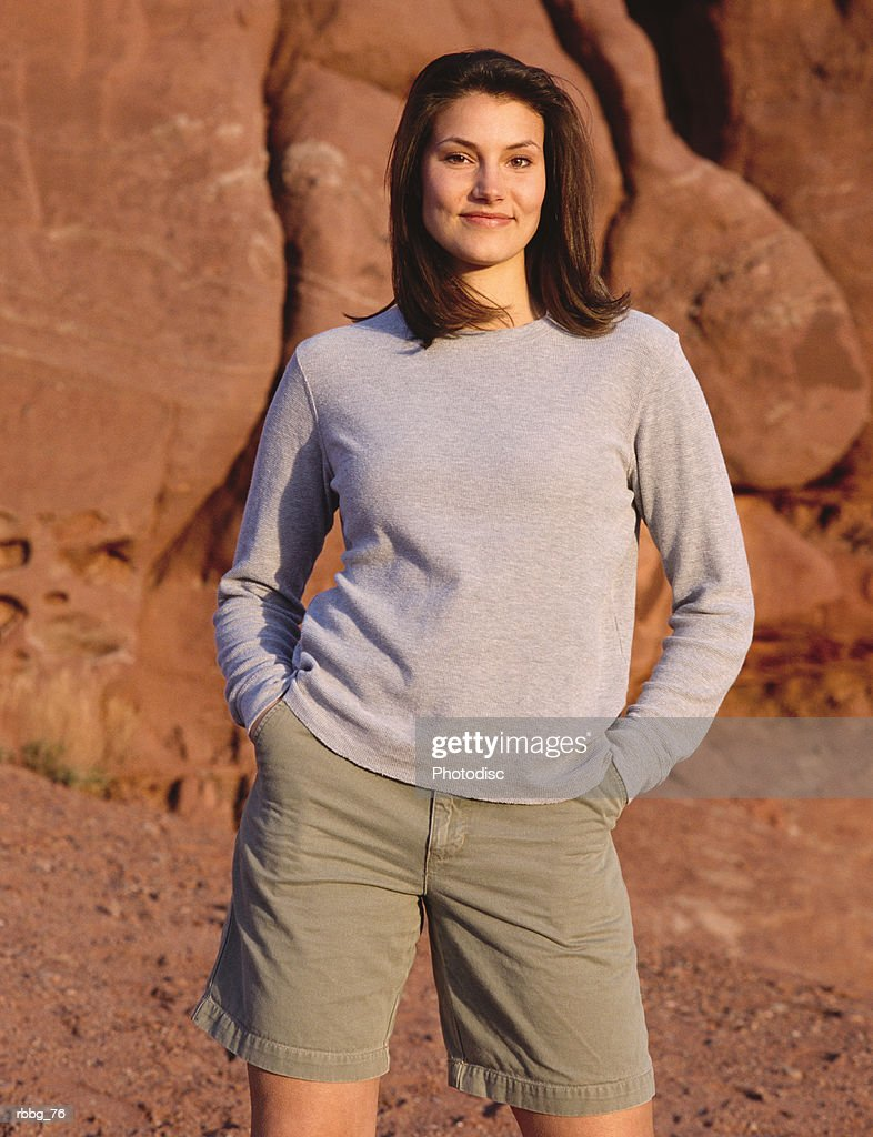 beautiful brown haired woman standing in a red colored rock background relaxing : Stockfoto