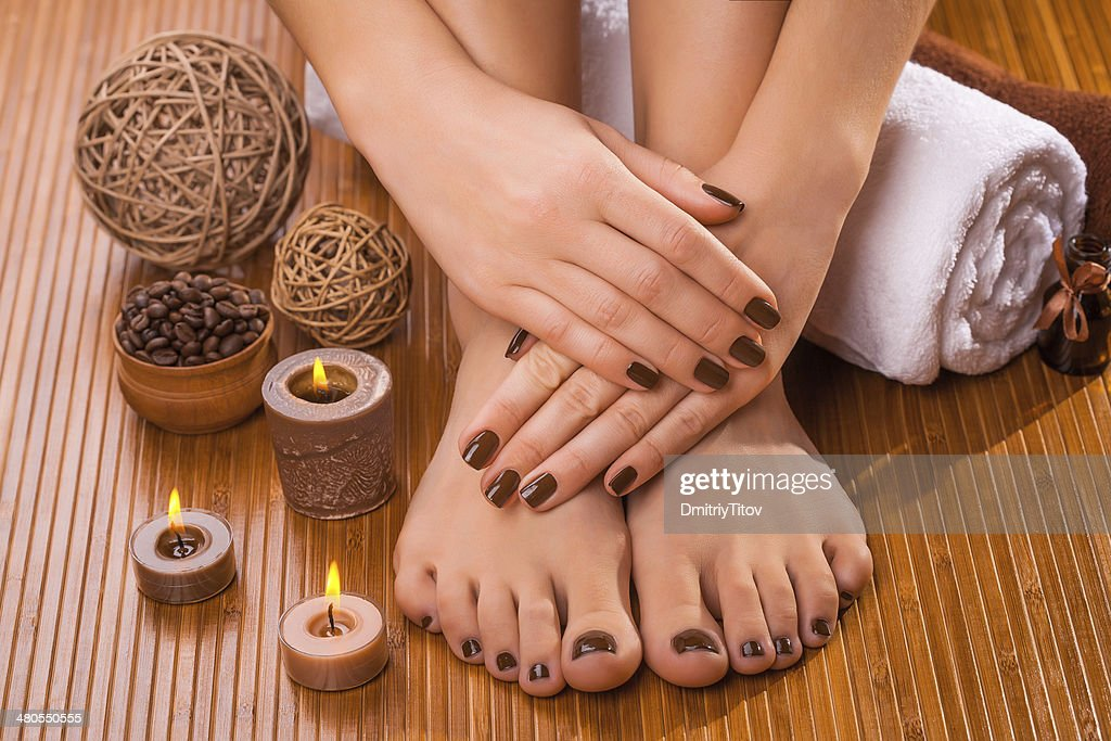 beautiful brown manicure and pedicure on the bamboo : Stock Photo