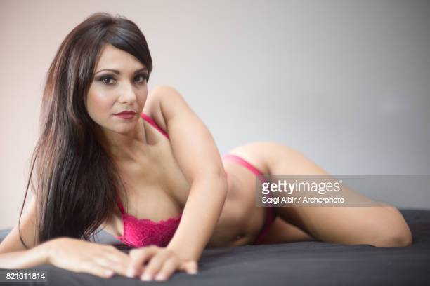 Beautiful brown-haired woman in fuchsia lingerie.