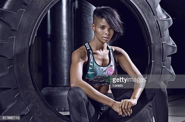Bela morena atlética mulher um posar com pneu em um ginásio