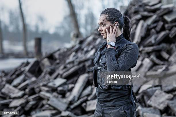 Beautiful brunette female military member standing at abandoned construction site