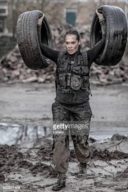 Mooie brunette vrouwelijke militairen lid opleiding hard op een verlaten bouwplaats