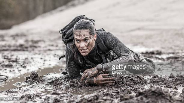 beautiful brunette female military swat security anti terror agent crawling during operations in muddy sand - military training stock pictures, royalty-free photos & images
