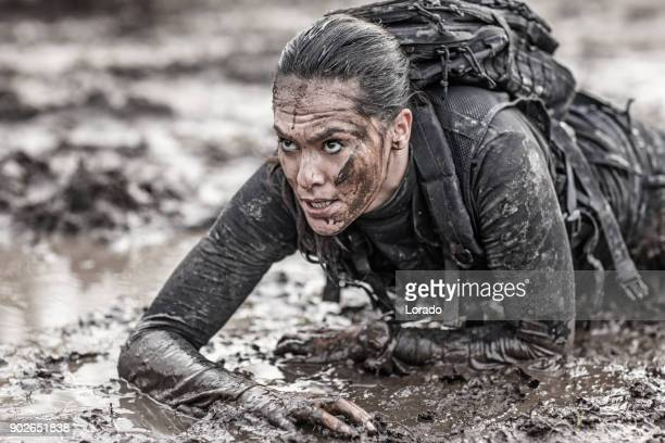 beautiful brunette female military swat security anti terror agent crawling during operations in muddy sand - sportkleding stock pictures, royalty-free photos & images