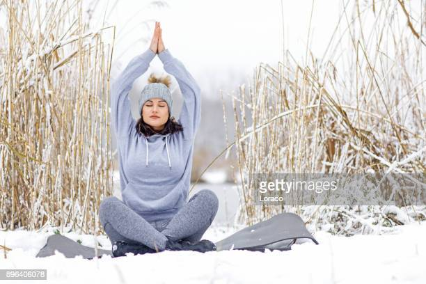 Beautiful Brunette Feminine Athletic Woman practicing yoga in the snow