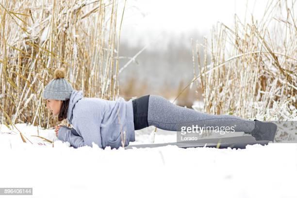 belle brunette féminin athletic femme pratiquer l'yoga dans la neige - une seule jeune femme photos et images de collection